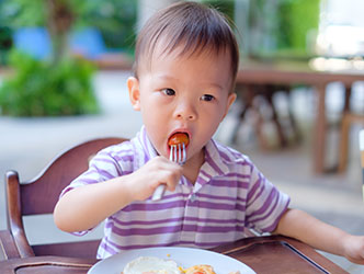 Baby sitting in high chair in a cherry tomato