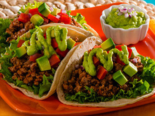 Soft corn tortilla filled with lettuce taco meat and topped with avocado sauce