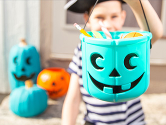 Kid dressed for Halloween holding a teal pumpkin filled with goodies.