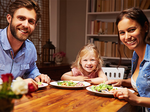 A young daughter is happy sitting between her parents illustrates the spirt of Family Meals Month.