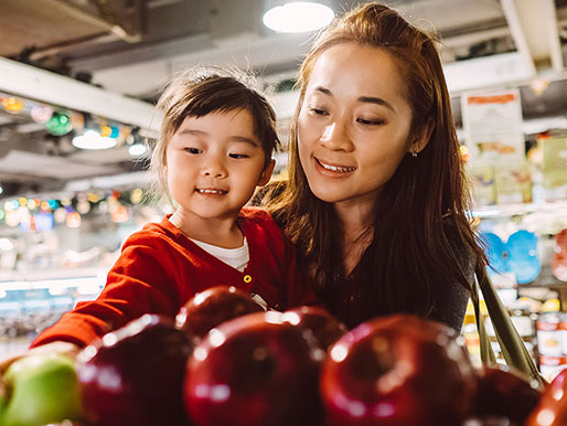 mom and daughter in grocery store shopping for apples