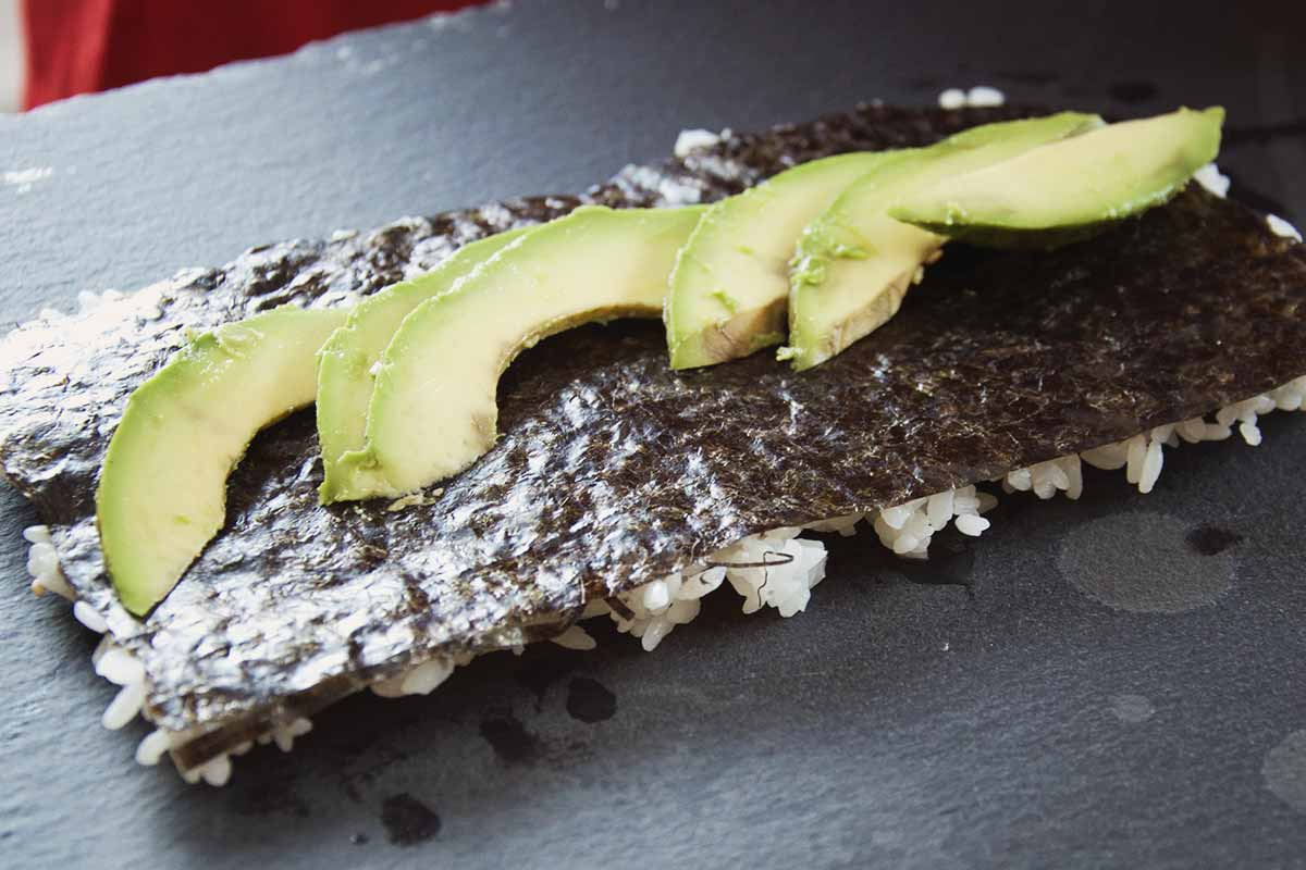 After the Nori and rice is flipped over, avocado is added to the middle equator of the sheet